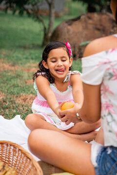 Niña recibiendo de su madre una deliciosa naranja