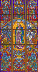 VIENNA, AUSTIRA - JUNI 24, 2021: The Immaculate Conception of Virgin Mary from Guadalupe on the stained glass in the Votivkirche church originaly by by Hans Schweiger (1963).