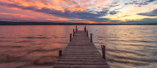 Banner of colorful sunset at a lake coast at a wooden pier.