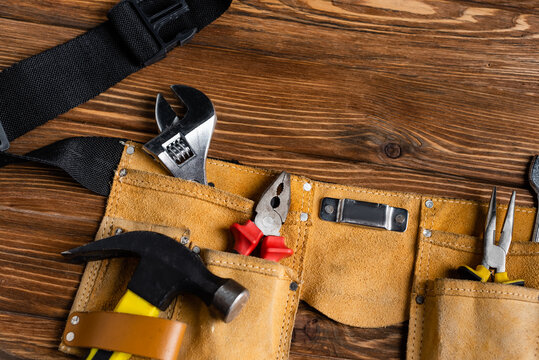top view of leather tool belt with hammer, pliers and wrench on wooden table, labor day concept