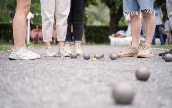 Friends playing petanque french game  on bocce court counting the results