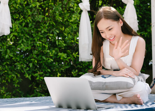 Portrait of beautiful korean chinese girl happy positive smiling cheerful lovely have online video call broadcast meet bloggers say hi wave hand sit outdoor on sofa patio furniture at terrace.