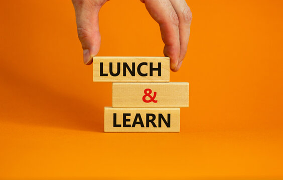 Lunch and learn symbol. Wooden blocks with concept words Lunch and learn. Beautiful orange background. Businessman hand. Copy space. Business, educational and lunch and learn concept.