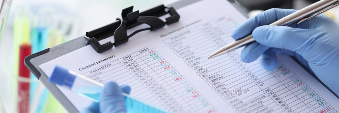 Researcher writes down chemical parameters of liquid in document