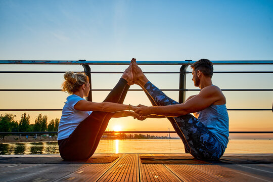Fit young couple doing acro yoga at pier by the sea. Healthy lifestyle. People outdoor sport activity on family vacation