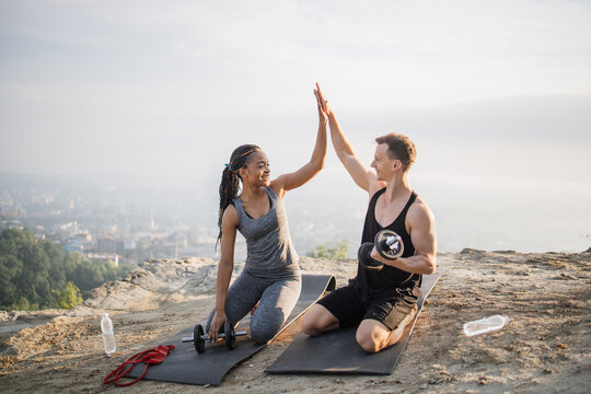 Happy multiracial couple in sportswear giving high five to each other while sitting on yoga mat outdoors. Black woman and caucasian man training with sport equipments.