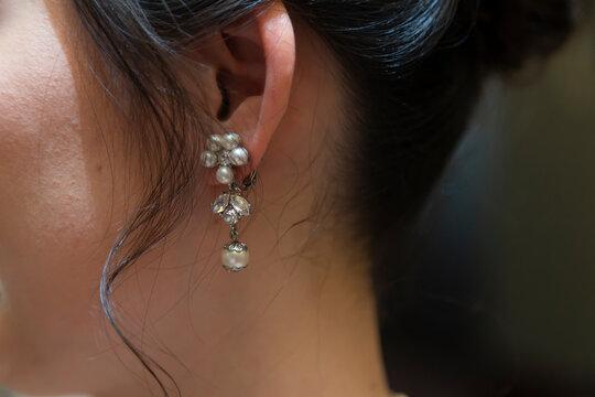 Pearl earrings on the bride's left ear