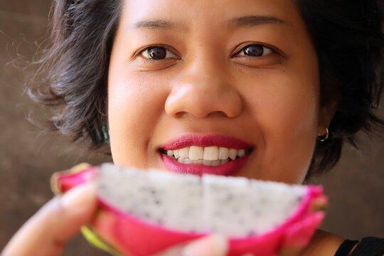 Portrait of Asia woman eating dragon tropic health fruit
