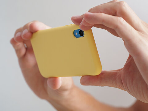 Close-up shot of a adult male hands taking photo or video, while using yellow cell phone.
