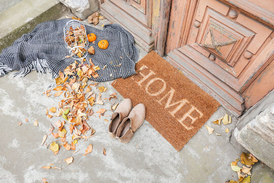 Doormat with plaid, shoes and leaves near entrance of house on autumn day