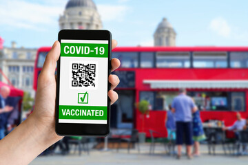 Hand holding mobile phone with covid-19 vaccinated on screen and red bus at London