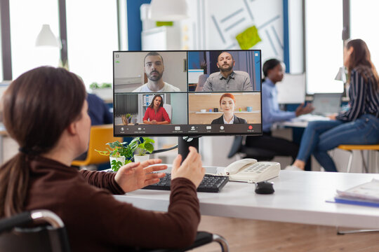 Handicapped paralyzed invalid employee during virtual meeting talking on videocall working from start up business office discussing with partners online using webcam. Businesswoman on video conference
