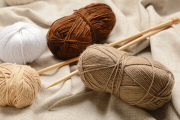 Knitting yarn and needles on fabric background, closeup