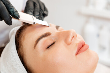 Fototapeta Procedure at the beauty salon. Cosmetologist cleans the client's forehead using a ultrasonic device. Close up. Concept of professional cosmetology obraz