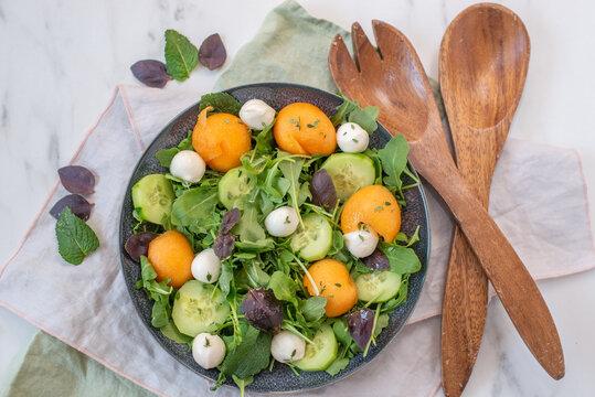 Fresh summer salad with arugula, mozzarella cheese and melon
