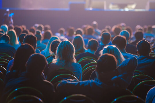 Unrecognizable people sitting in dark auditorium