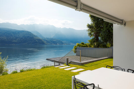 Private terrace overlooking Lake Ceresio in Switzerland. In front of a beautiful green lawn table and chairs.