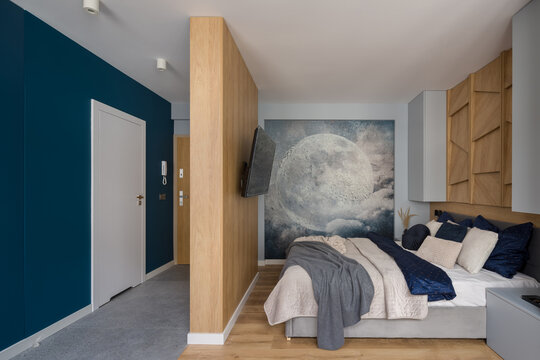Stylish bedroom with wooden walls and decorative wall mural