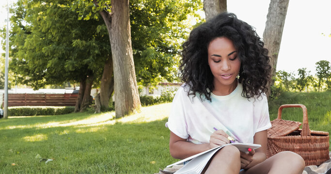 curly african american woman writing in notebook in park.