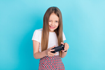 Photo of nice brown hair little girl playstation wear white t-shirt isolated on blue color background Wall mural