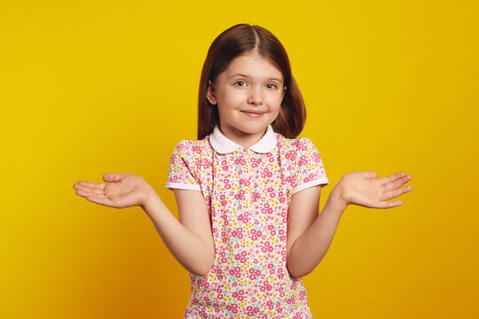 Young girl kid with arms out, shrugging her shoulders, saying who cares, so what, I dont know, isolated over yellow background