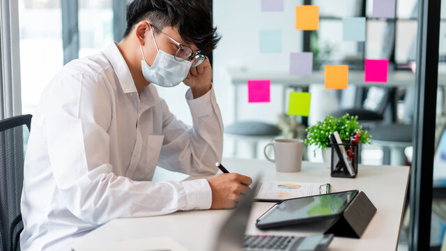 Freelancers wearing protective masks keeping distance as preventive action when working together