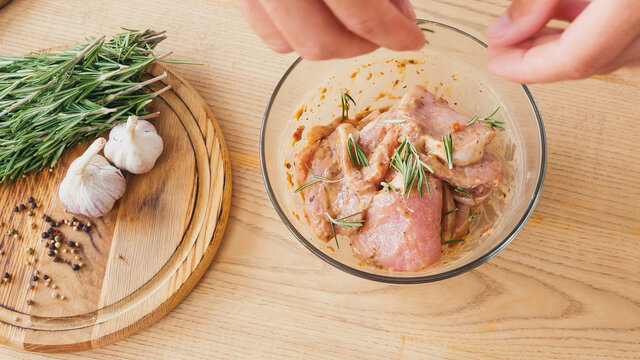 top view of chef seasoning marinated sliced chicken with rosemary in bowl
