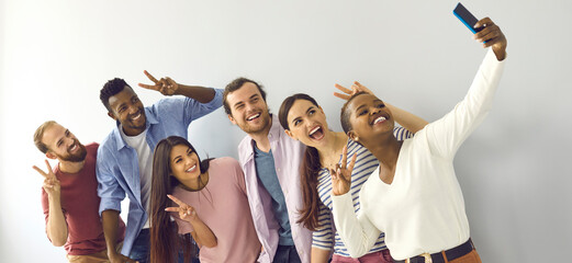 Happy cheerful laughing young adult diverse college student friends doing V sign hand gesture...