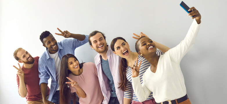 Happy cheerful laughing young adult diverse college student friends doing V sign hand gesture taking group phone selfie picture in studio, enjoying best time of life, making memories together. Header
