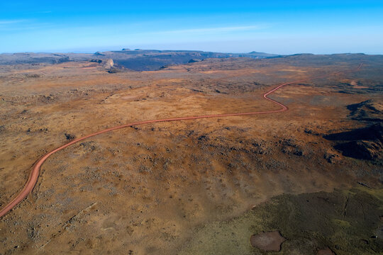 Aerial view of a dirt road crossing the strange, inhospitable landscape of the Sanetti plateau. Mars landscape in Bale mountains national park, home of rare animals. Travel around Ethiopia.