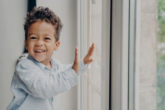 Portrait of little joyful black kid with adorable smile having fun at home