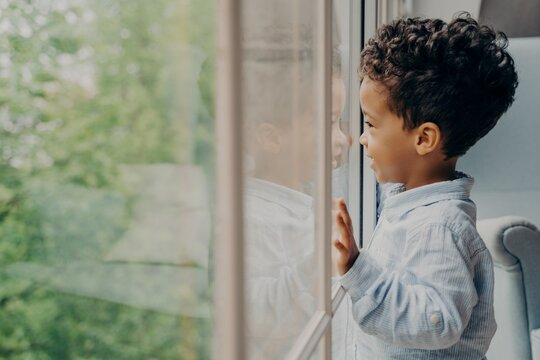 Lovely afro american kid in light blue shirt looking out of window