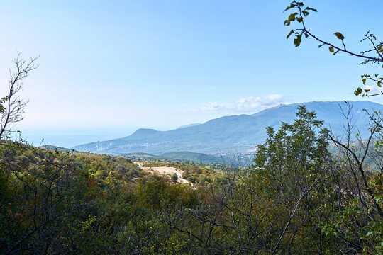 View of the city of Alushta in Crimea from the Demerdzhi mountain. Valley of ghosts in the highlands. Outdoor walks in the hills. Beautiful landscape from the top. Forest in bright, clear sunny weathe