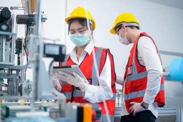 Obraz Quality control (QC) engineer monitoring and checking machine system in manufacturing factory - fototapety do salonu