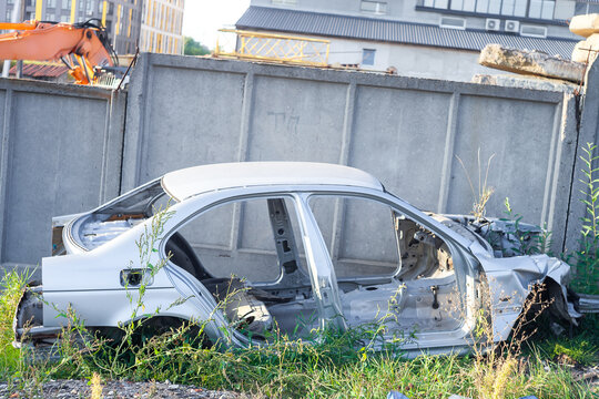 Old wrecked car in junkyard. Destroyed metal vehicle at backyard near concrete wall, side view