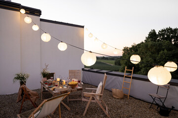 Fototapeta Beautifully decorated roof terrace in natural boho style with a dining table full of food at summer time. Festive dinner for a small group of friends at dusk outdoors obraz