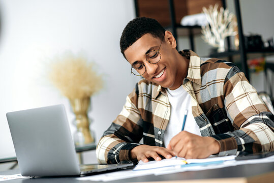 Smart positive latino young man with glasses, sitting at the table, using a laptop, taking notes, studying or working online, listening to a webinar, gaining knowledge, smiling