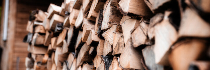 a woodpile with harvesting and stacked firewood of chopped wood for kindling and heating the house. firewood of the birch tree. banner