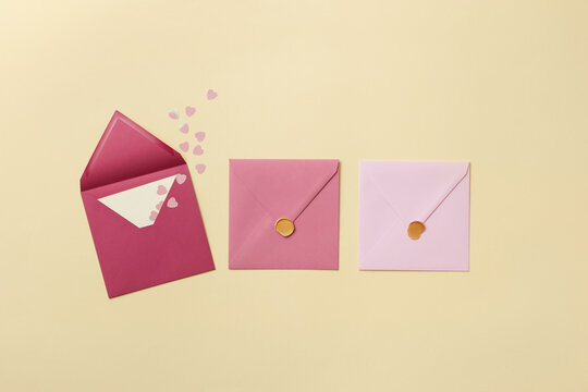 Pink envelope with paper hearts and closed envelopes