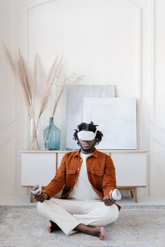Man in VR glasses doing yoga at home