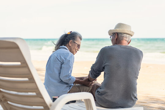 Happy Asian family, senior couple sitting on chairs with backs on beach travel vacation talking together, Romantic elderly enjoy Travel summer vacation, plan life insurance retirement couple concept