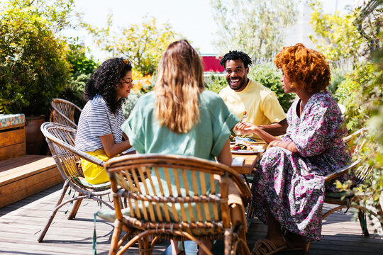 Black man meeting with diverse girlfriends in outdoor cafe