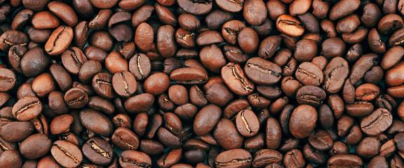 Coffee bean background. Dark, brown roasted coffee beans. Scattered coffee beans. Background for advertising.