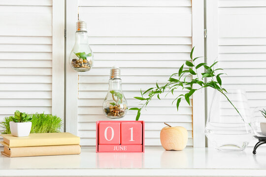 Cube calendar with date JUNE 1, books and houseplants on table in room