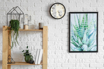 Fototapeta Book shelf with clock and picture hanging on brick wall obraz