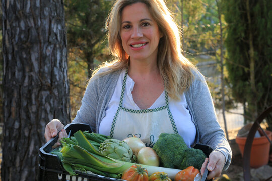woman with a box of fresh vegetables and fruits