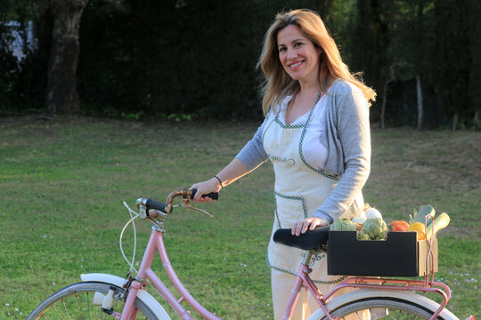 woman with bycicle with green healthy vegetables food