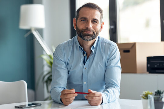 Confident mature man explaing something looking at camera while doing video call in the office at home.