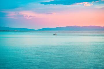Obraz Bright beautiful sunrise at sea. A scenic view of a colorful sky above the ocean. Orange and blue clouds. Beautiful landscape of a ocean bay. Scenic view of mountains and sea. Colorful sunrise sky - fototapety do salonu
