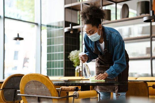 Black waitress wearing apron cleaning table while working in cafe
